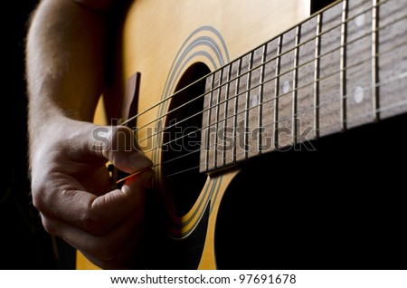 Strumming an acoustic guitar - stock photo