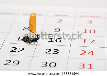 stubbed out cigarette on calendar, quit smoking concept - stock photo