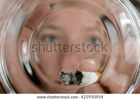 Stubbing put out a cigarette in ashtray - stock photo