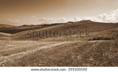 Stubble Fields on the Hills of Sicily at Sunset, Vintage Style Sepia  - stock photo