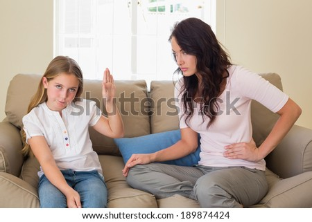 Stubborn girl showing stop gesture to mother while sitting on sofa at home - stock photo