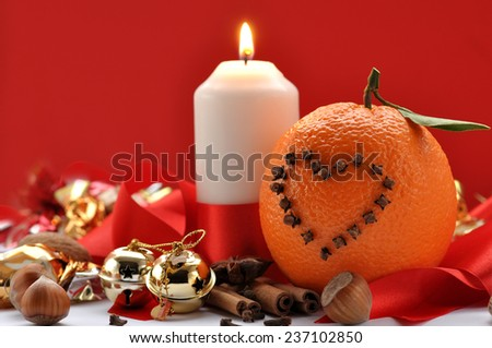 Studded oranges and candle - stock photo