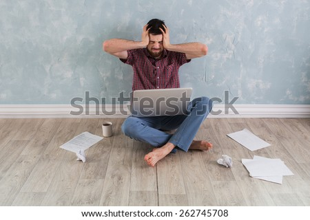 studenh holding his head with his hands. Around the scattered papers. Businessman gets stress - stock photo