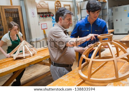 Student and teacher standing in a woodwork class and working on a structure - stock photo