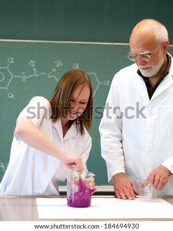 Student and teacher to stir something in a glass flask - stock photo