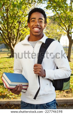 Student at school holding books and a book bag  - stock photo