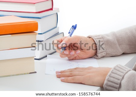 Student at the desk with heap of books taking notes  - stock photo