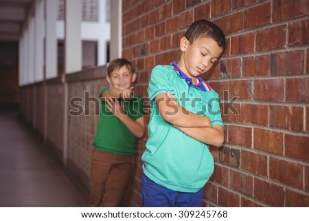 Student being bullied by a fellow student on the elementary school grounds - stock photo