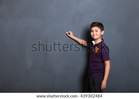 student boy  beside a big blackboard for drawing, writing and show the place for your text, - stock photo