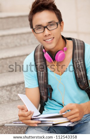 Student boy sitting on steps and studying - stock photo