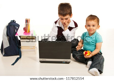 Student boy using laptop  while his little brother eating an apple and sitting together on floor - stock photo