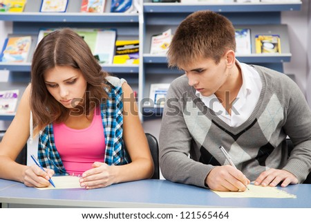 Student cheating at exam, looking at a friend's writing - stock photo