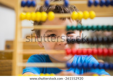 Student doing maths on abacus at elementary school - stock photo