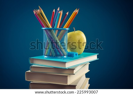 Student equipment with pile of books, apple and color pencils, back to school concept.