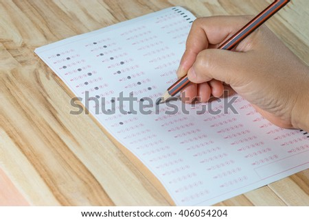 Student filling out answer sheets with pencil - stock photo