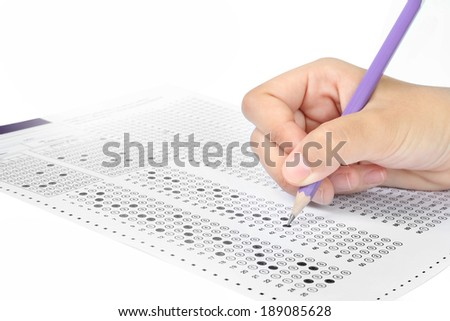 Student filling out answers to purple answer sheet with purple pencil - stock photo