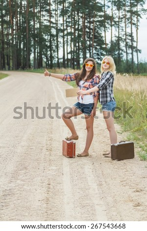 Student friends on summer rural vacations are wearing sunglasses, denim hot pants and shirtshitchhike with cardboard on dirt field road - stock photo