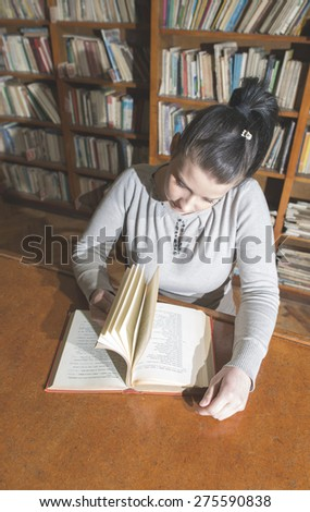 Student girl in a library. Looking at book