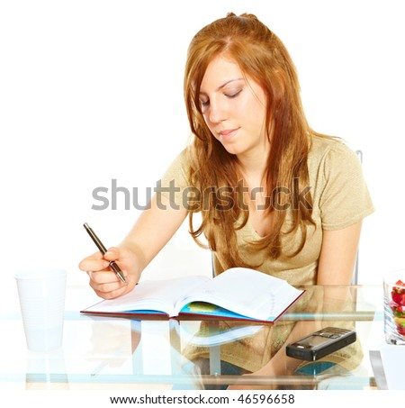 Student girl learning at desk with notebook with pen in hand