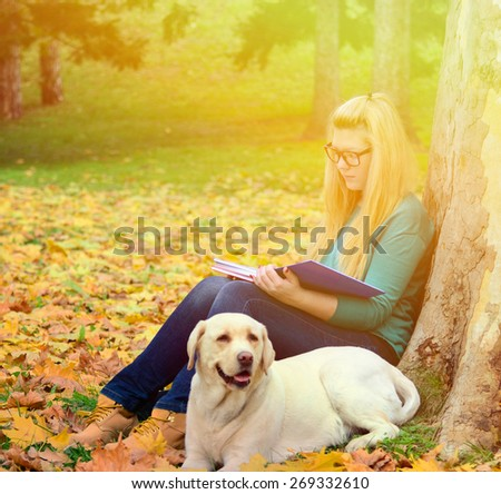 Student girl learning in nature with dog - stock photo