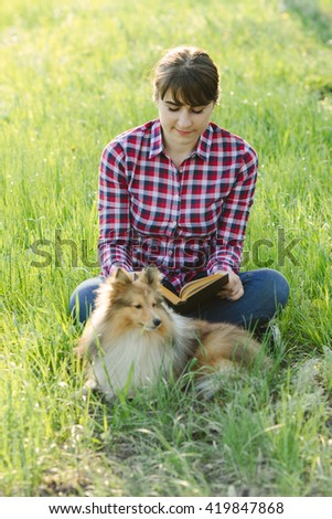 Student girl learning in nature with dog in the park on the grass