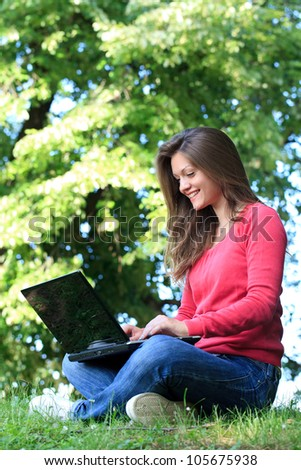 Student girl looking in laptop and smiling in park - stock photo