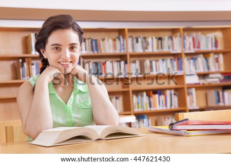 Student girl reading a book at the university library - stock photo