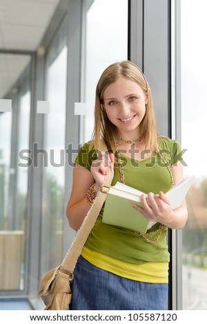 Student girl reading book by high school library window