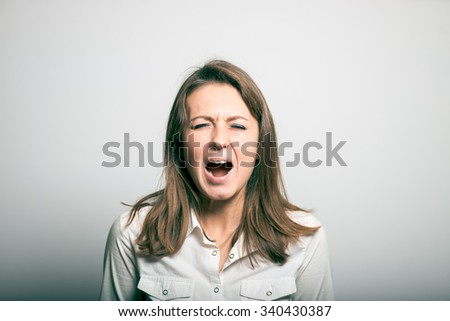 student girl shouts. office manager. studio photo on a gray background