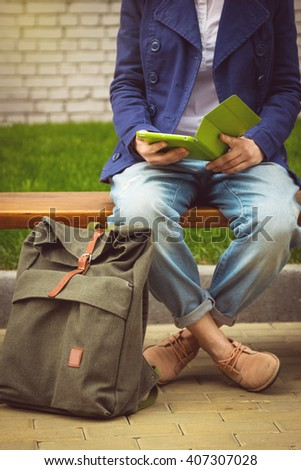 Student girl sitting on the bench with tablet and backpack