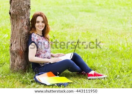 Student girl sitting on the grass and using laptop computer at the university campus