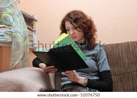 Student girl sitting on the sofa, looking at book and reading.
