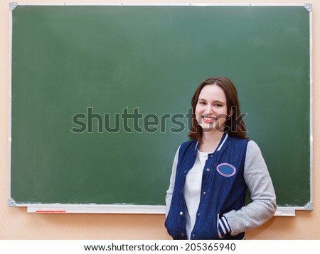 Student girl standing near blackboard in the classroom