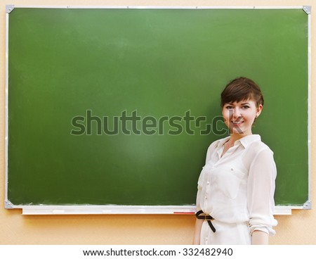 Student girl standing near clean blackboard in the classroom
