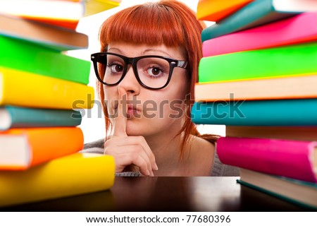 student girl with finger on mouth, peeking between stack of books,  isolated