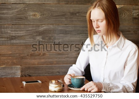 Student girl with ginger hair sitting at the table at a cafe, enjoying coffee and eating dessert after classes at college. Young female office worker relaxing at a coffee shop after hard day at work - stock photo