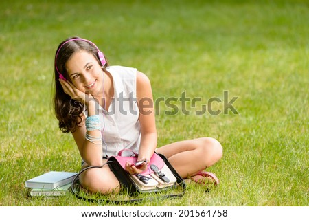 Student girl with pink headphones sitting on grass summer - stock photo
