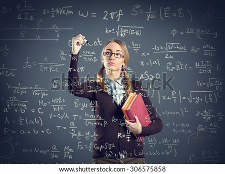 Student girl writing formulas on transparent wall front her  - stock photo