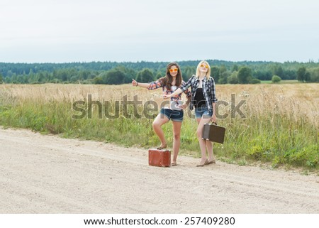 Student girls wearing sunglasses hitchhike on country road - stock photo