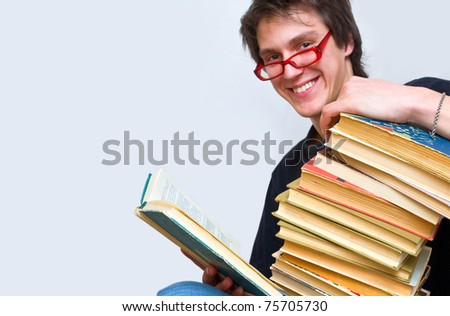 student happily smiles opening one of his textbooks