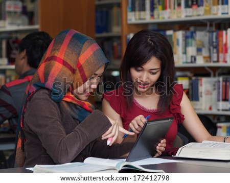 Student having discussion in college library - stock photo