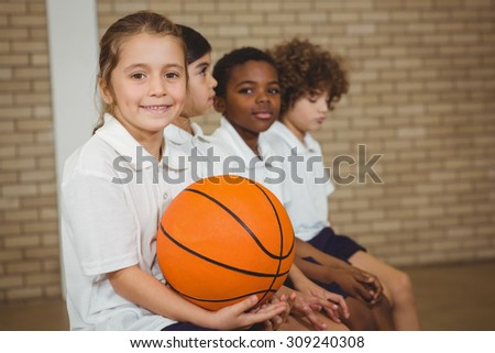 Student holding basketball with fellow players at the elementary school - stock photo