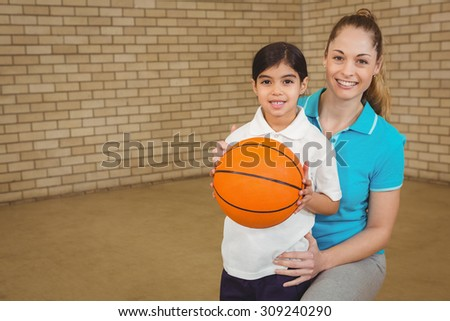 Student holding basketball with teacher at the elementary school - stock photo