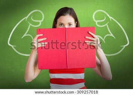 Student holding book over face against green chalkboard