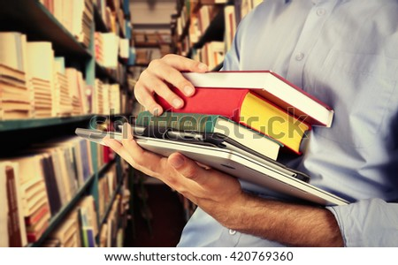Student holding books and laptop in library - stock photo