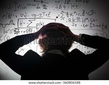 Student holding his head looking at complex math formulas on whiteboard. Mathematics and science exam concept, problem to solve. Harsh lighting and bended crop to show chaos in his mind.