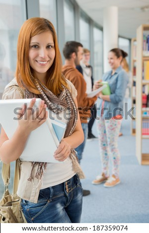 Student holding laptop with friends in background at school library - stock photo