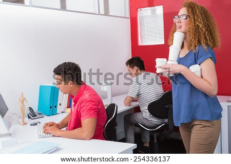 Student holding pile of coffee cup at the college