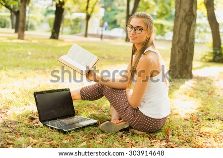 Student, in business style casual dressed, sitting in park working on laptop at campus