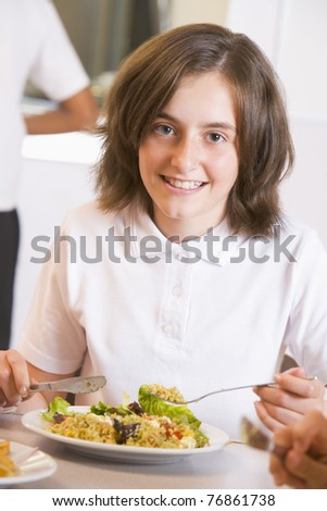 Student in cafeteria eating lunch